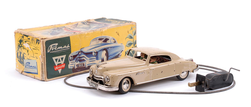 Arnold (made in Western Germany) Primal clockwork Coupe - beige, driver and lady passenger, manual wind-up remote control cable attached and in working order with remote steering, gold tinplate base - Good in Fair original box (one replacement end to box