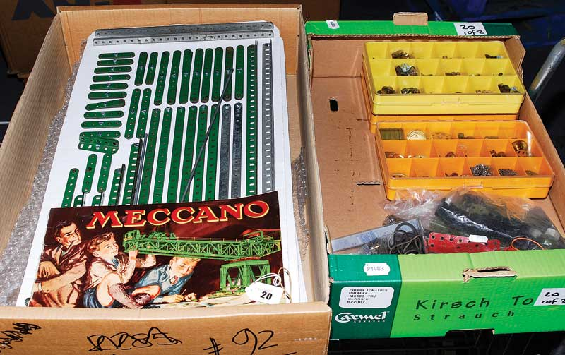 """Meccano a quantity of red, green, blue and gold parts including perforated strips, 24"""" angle girders, wheels, tyres, flanged plates, flanged sector plates, gears and a number of other useful components, all screwed to 4 backing boards"""